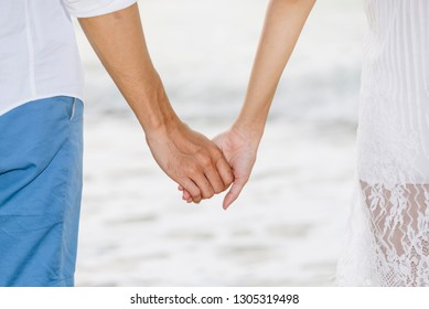 Closeup of couple holding hands togethers while walking on the beach at sunset. Love and valentine concept.