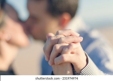 Closeup of couple holding hands while they are kissing with shallow dof