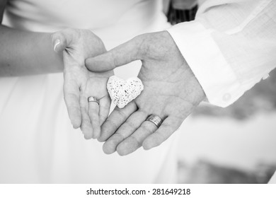 Closeup of a couple holding a heart-shaped coral during a wedding ceremony on the beach. Destination wedding.