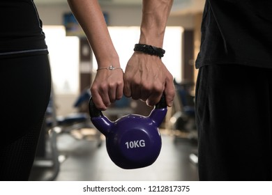 Close-up of Couple Holding Kettlebell Showing Some Love
