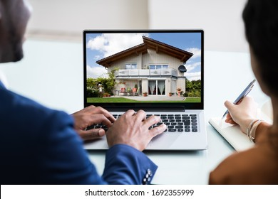 Close-up Of A Couple Looking For New House On Laptop