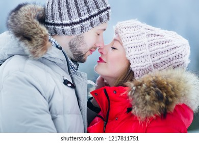 a close-up of a couple in love who have closed their eyes and want to kiss. guy and girl in warm winter clothes