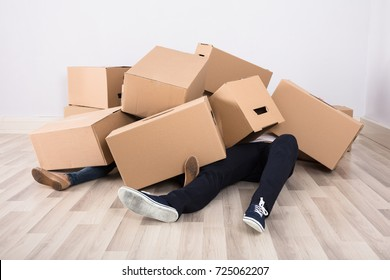 Close-up Of Couple Lying Under The Heap Of Cardboard Boxes On Floor