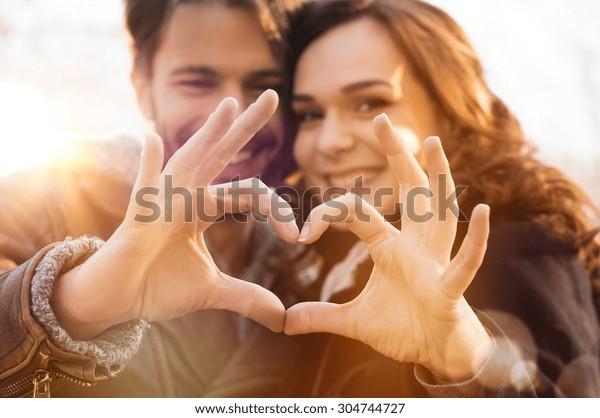 手で心の形を作る夫婦の接写
