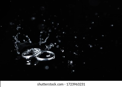 close-up of couple silver ring on black background, water drop and splash on ring