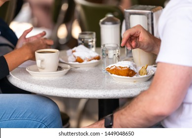 Closeup of couple sitting outside at sidewalk cafe by table drinking chicory coffee and eating deep fried beignet donut powdered with sugar