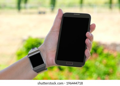 Closeup of couple smartwatch and phablet as the concept of wearable technology