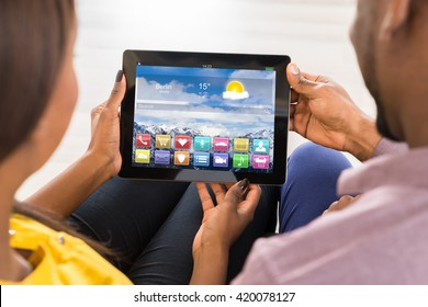 Close-up Of Couple Using Digital Tablet With Multicolored Apps On It