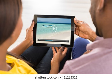 Close-up Of A Couple Watching Video On Digital Tablet