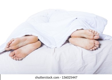 Close-up of couple's feet who had a fight on bed