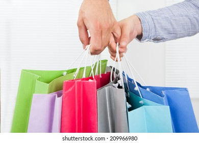 Closeup of couple's hands holding multicolored shopping bags in house