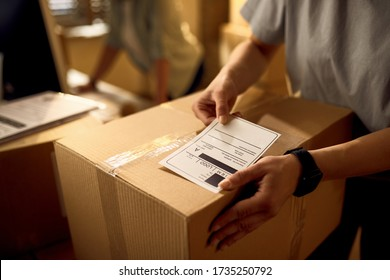 Close-up of courier attaching address label on a package while working in the office.