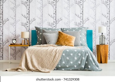 Close-up of cozy bed with gray bedsheets and beige blanket against white wallpaper with forest motif