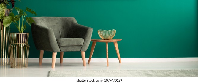 Close-up of a cozy, dark armchair and a wooden coffee table in a luxurious, green living room interior with golden decorations