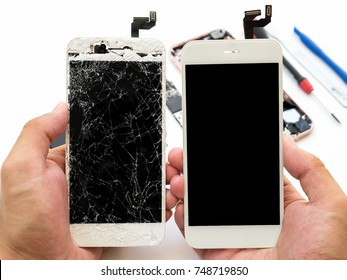 Close-up of cracked smartphone screen compare with new screen in technician hand on blurred smartphone component background