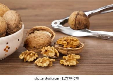 Close-up of cracked walnuts with nutcracker on light wooden background