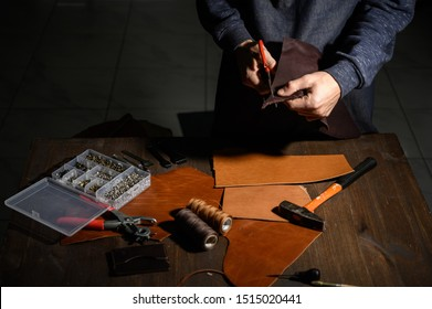 Closeup of craftsman cutting leather handicraft.Craftsman cutting into a hide. process of manufacturing footwear parts