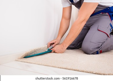Close-up Of A Craftsman Fitting Carpet On Floor With Cutter