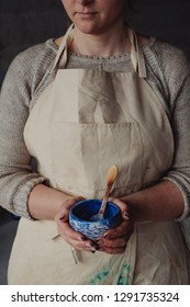 Close-up craftswoman in beige apron holding hand made ceramic pottery designer painted bowl at pottery studio