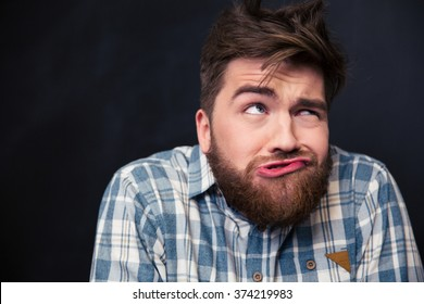 Closeup of crazy young man in plaid shirt joking and grimacing over black background