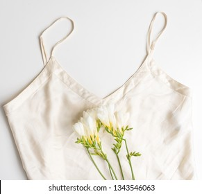 Closeup of cream silk camisole with freesia flowers from above on white background