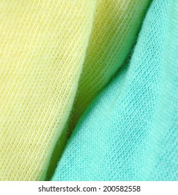 Closeup of creases between a yellow and blue cotton fabric.