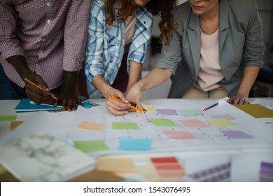 Closeup of creative business team working on design project focus on table with roadmap and colorful stickie notes, copy space