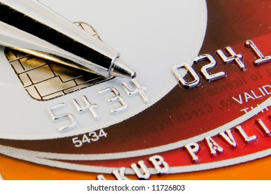 a close-up of credit card with chip and numbers and a pen atop