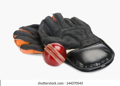 Close-up of a cricket ball with a pair of wicket keeping gloves