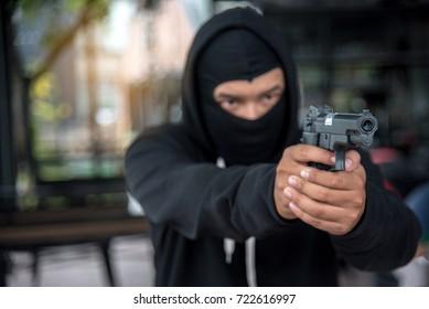 Closeup of criminal aiming gun.  Crime and robbery concept.