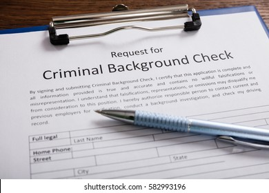 Close-up Of Criminal Background Check Application Form With Pen At Desk