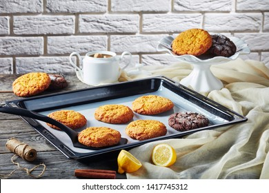 close-up of Crinkle cookies. Cracked lemon biscuits. Chocolate biscuits, lemon crinkle cookies on a baking pan and on a dish at the background of a brick wall, view from above