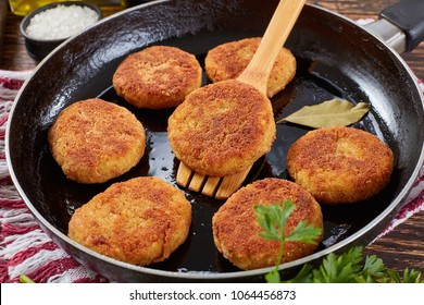 close-up of crispy rice cutlets of leftover rice with crumbled cheese and greens on a skillet on wooden table with uncooked cutlets, paneer cheese cubes at background, indian recipe, view from above