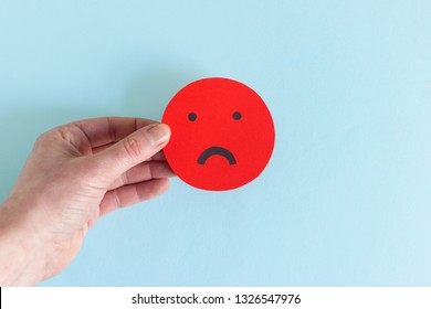 Closeup of crop hand showing round smiley of red color with unhappy rating on blue background