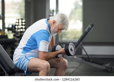 Closeup crop horizontal portrait of elderler man on daily training in gym. Senior adult concentrated serious athlete with good wellbeing and great fit holding sports facilities. Concept of lifestyle.