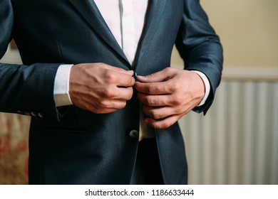 Close-up of a cropped frame of a business stylish man buttoning his jacket, standing in a stylish office with designer repair.
