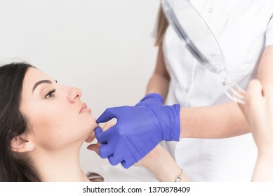Closeup cropped image of doctor's hands checking patient chin after corrective procedure, Aesthetic corrective treatments concept