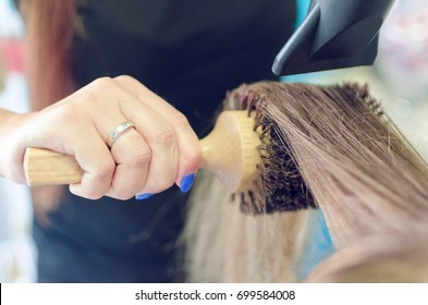 Closeup and cropped image of hairdresser blow drying woman hair with brush and hair dryer.