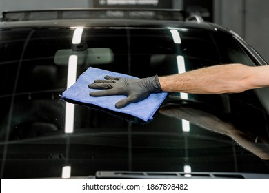 Closeup cropped image of hand of young man worker of auto service, wiping and polishing the windscreen of modern black car with blue microfiber cloth. Car wash concept.