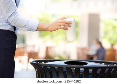 Closeup cropped image woman's hand throwing empty paper coffee cup in recycling bin, isolated outside, trees background. Recycling, eco friendly approach concept. Keep streets, city, earth clean