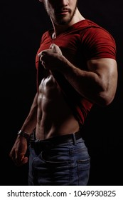 closeup cropped image of young sexy male in red T-shirt and jeans doing a striptease.taking off T-shirt.naked torso.press. man's coquety.flirtation. demonstrating body