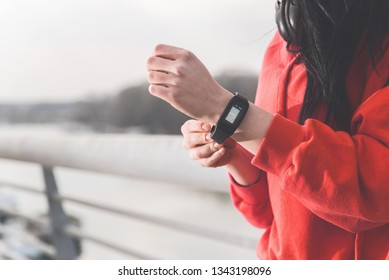 Closeup cropped photo of female runner putting a pedometer on her wrist, Sports equipment and gadgets concept