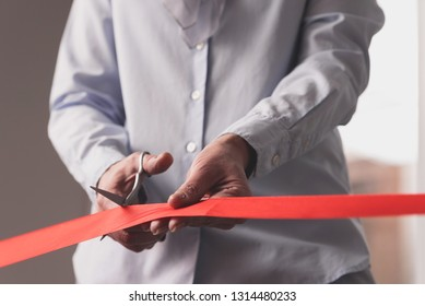 Closeup cropped photo of senior female hands cutting red ribbon with scissors  on opening ceremony, Passive income and rental business concept