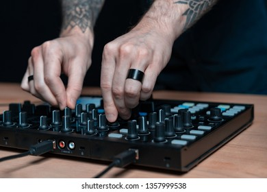 Close-up and cropped photo tattoo hands of professional DJ man creative music inside house room studio with black dark wall interior. He using spacial controller instrument