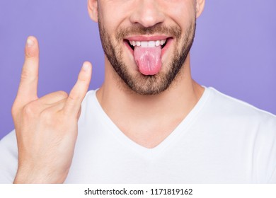 Close-up cropped portrait of attractive, trendy, stylish, toothy man with healthy teeth, showing tongue out, rock-n-roll sign symbol, over pastel violet purple background