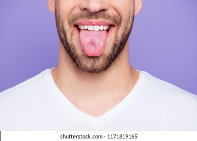 Close-up cropped portrait of attractive, trendy, stylish, toothy man with healthy teeth, showing tongue out, over pastel violet purple background