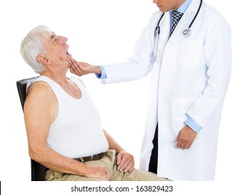Closeup cropped portrait of a doctor performing oral, throat, neck physical exam  holding face looking inside mouth of elderly senior mature man sitting on black chair, isolated on a white background.