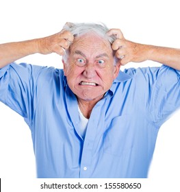 A close-up cropped portrait of an elderly, desperate, mad, looking crazy old man, going insane, pulling out his hair, isolated on a white background.Human emotions extremes. Loneliness, mental health