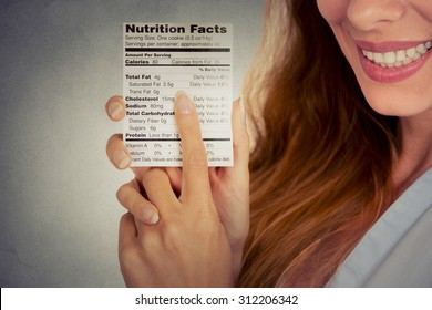 Closeup cropped portrait image woman reading healthy food nutrition facts isolated on gray wall background