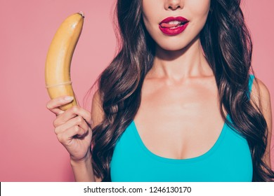 Close-up cropped portrait of nice cool alluring adorable charming glamorous delicate sweet wavy-haired lady holding in hands banana licking red lips isolated over pink pastel background